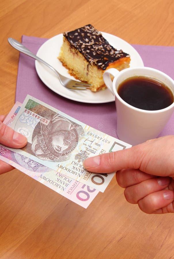 Betala för ostkaka och kaffe i kafét, finansbegrepp royaltyfria foton