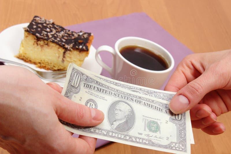Betala för ostkaka och kaffe i kafét, finansbegrepp royaltyfri foto