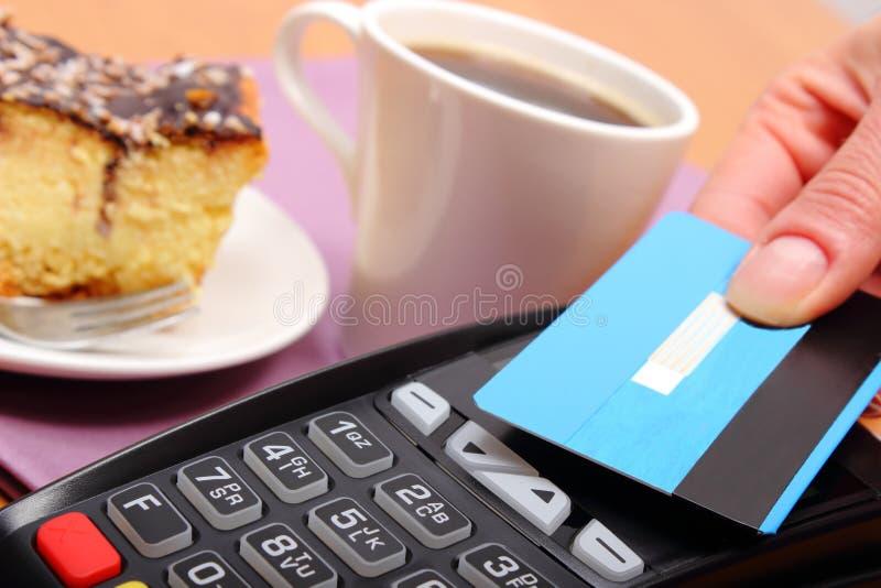 Betala med den contactless kreditkorten för ostkaka och kaffe i kafét, finansbegrepp royaltyfria bilder