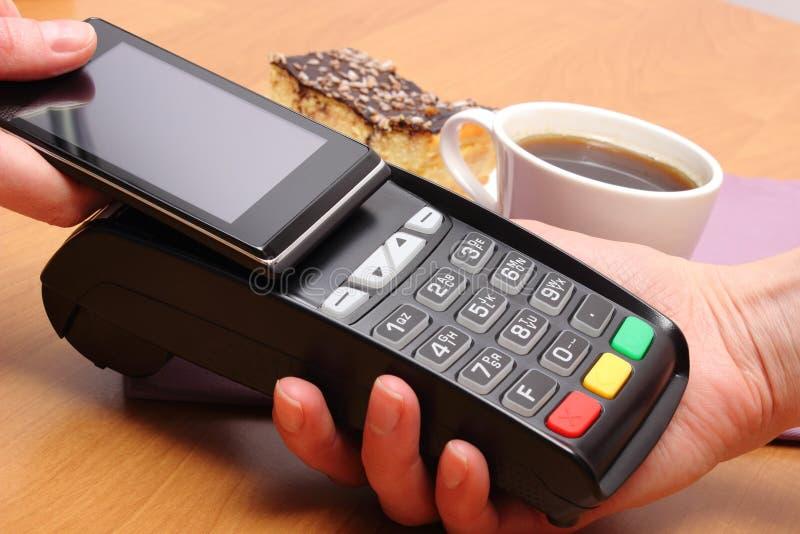Betala med mobiltelefonen med NFC-teknologi för ostkaka och kaffe i kafé, finansbegrepp fotografering för bildbyråer
