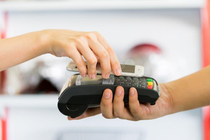 Betala till och med smartphonen genom att använda NFC royaltyfri foto