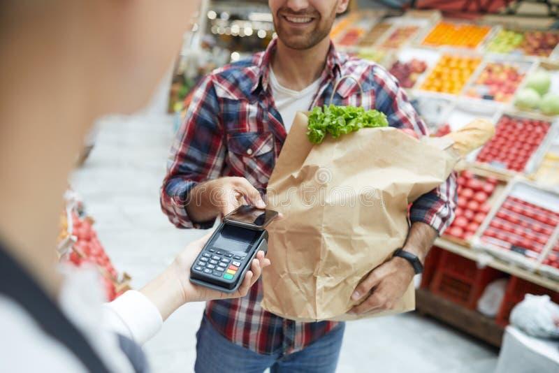 Betala vid Smartphone i supermarket fotografering för bildbyråer