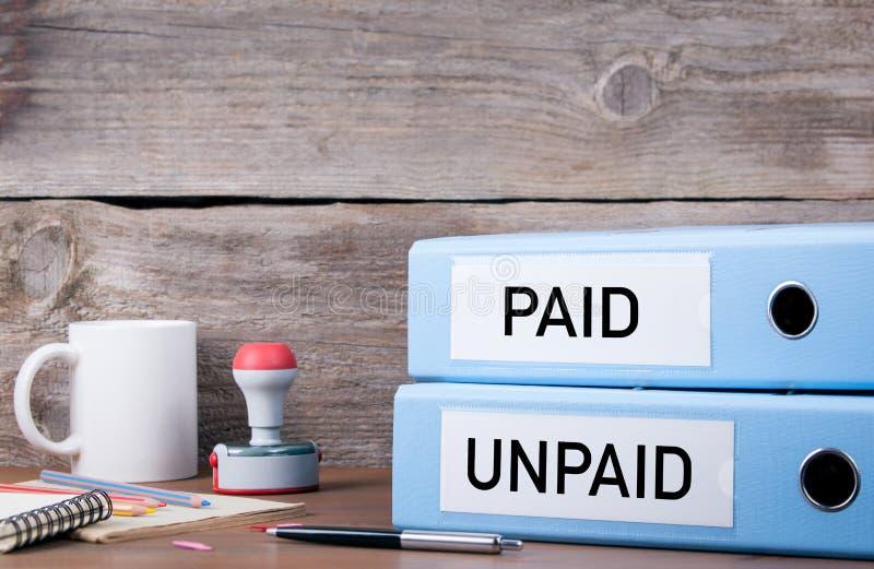 Betald och obetalt Två limbindningar på skrivbordet i kontoret Affärsbac arkivbild