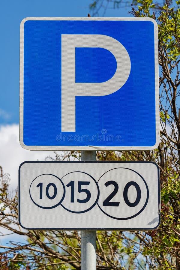 Betald parkering för vägmärke mot gröna träd och blå himmel i closeup för solig dag royaltyfria bilder