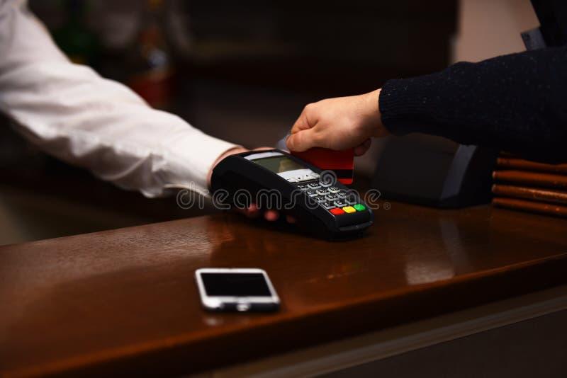 Betaling met creditcard De mannelijke hand zet bankkaart in lezer stock foto's