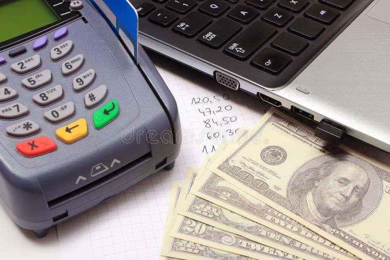 Betalingsterminal met creditcard, geld, laptop en financiële berekeningen stock afbeeldingen