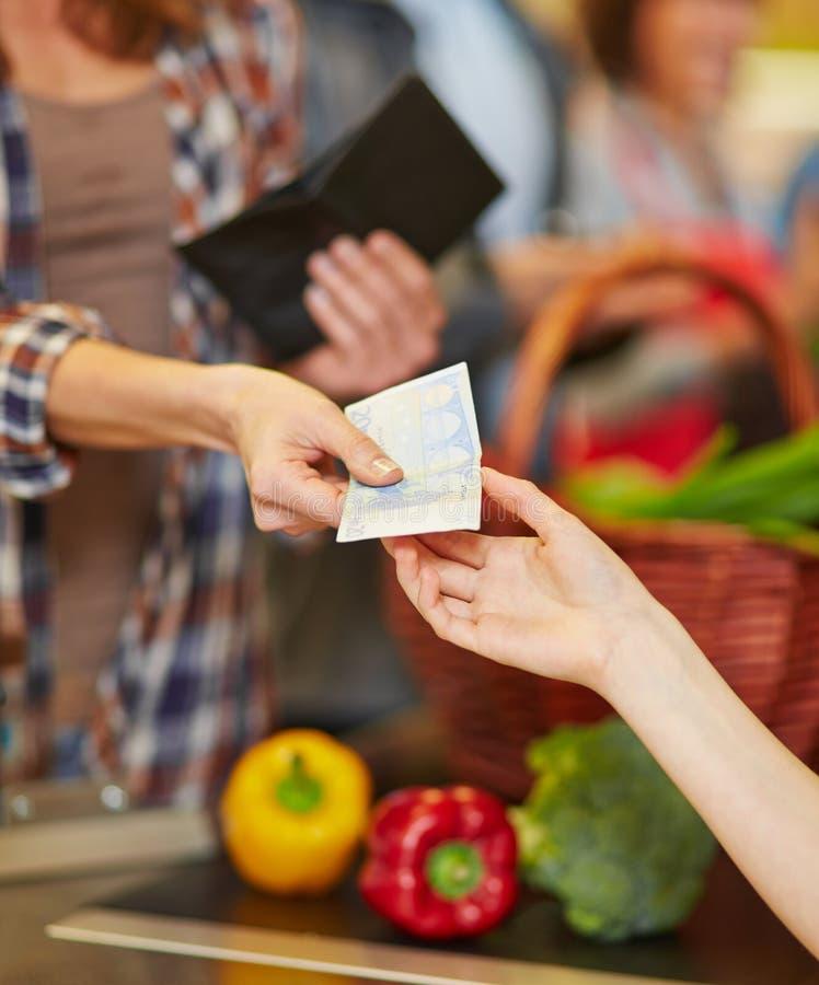 Betalning med kontanta pengar i supermarket royaltyfria bilder