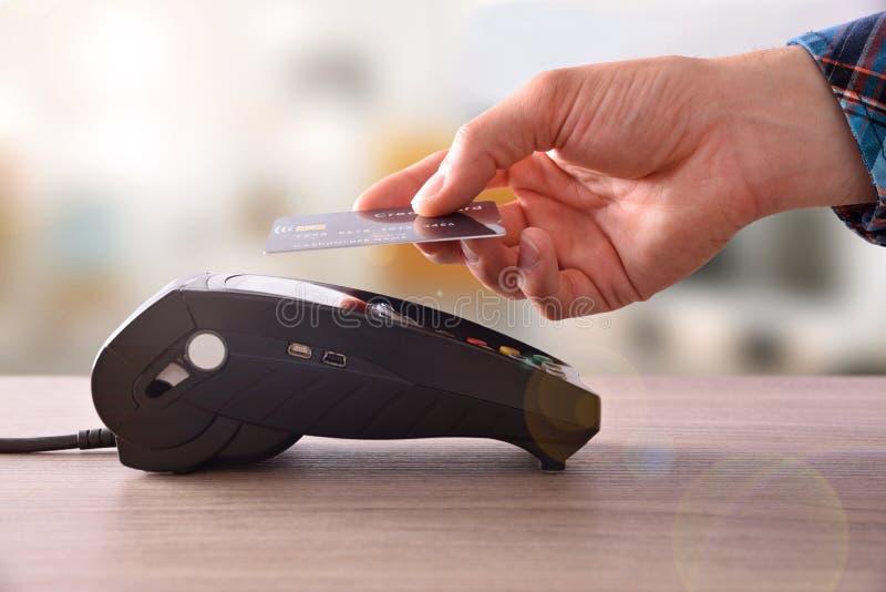 Betalning på en handel till och med contactless kort och NFC-teknologi arkivfoto