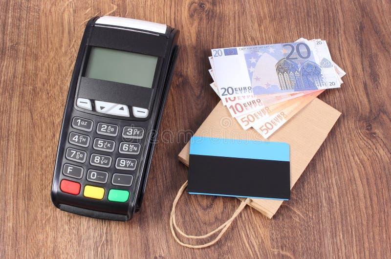 Betalningterminal med kreditkorten, valutor euro och pappersshoppingpåsen, begrepp av att betala för att shoppa arkivfoto