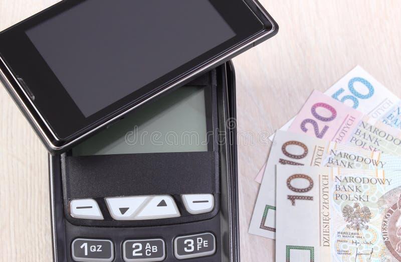 Betalningterminal med mobiltelefonen med NFC-teknologi och polermedelvaluta Begrepp av cashless betala för att shoppa eller produ royaltyfria foton