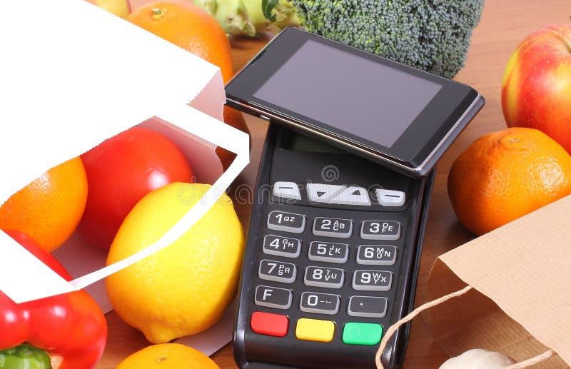 Betalningterminal och mobiltelefon med NFC-teknologi, frukter och gr?nsaker, cashless betala f?r att shoppa begrepp royaltyfria bilder