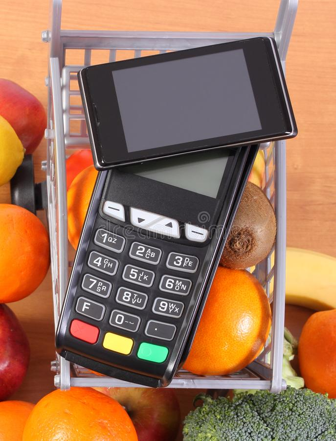 Betalningterminal och mobiltelefon med NFC-teknologi, frukter och gr?nsaker, cashless betala f?r att shoppa begrepp arkivfoto