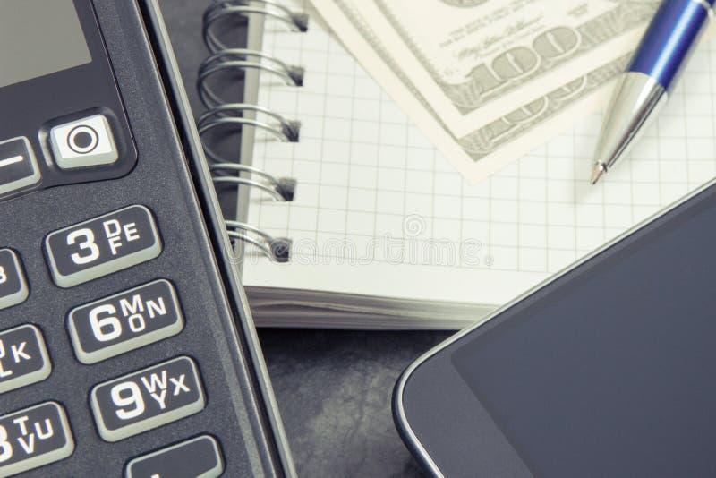 Betalningterminal, smartphone med NFC-teknologi för cashless betala i olika ställen, notepad och valutadollar fotografering för bildbyråer