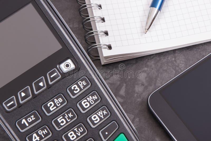 Betalningterminal, smartphone med NFC-teknologi och notepad för anmärkningar Cashless betala och affärsidé arkivbilder