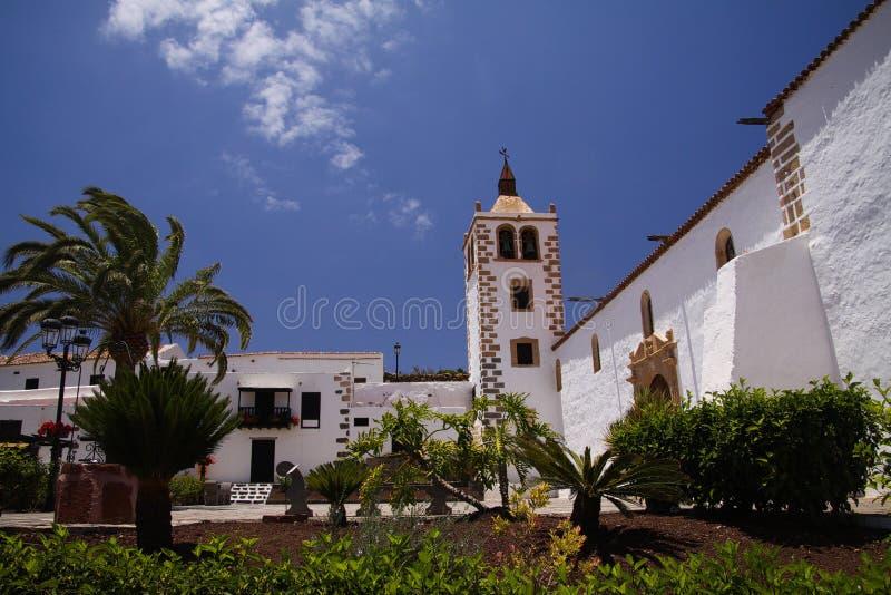 BETANCURIA FUERTEVENTURA - JUIN 14 2019: Sikt över trädgård med palmträd på gammal vit kyrka med klockatornet mot blå himmel arkivbilder