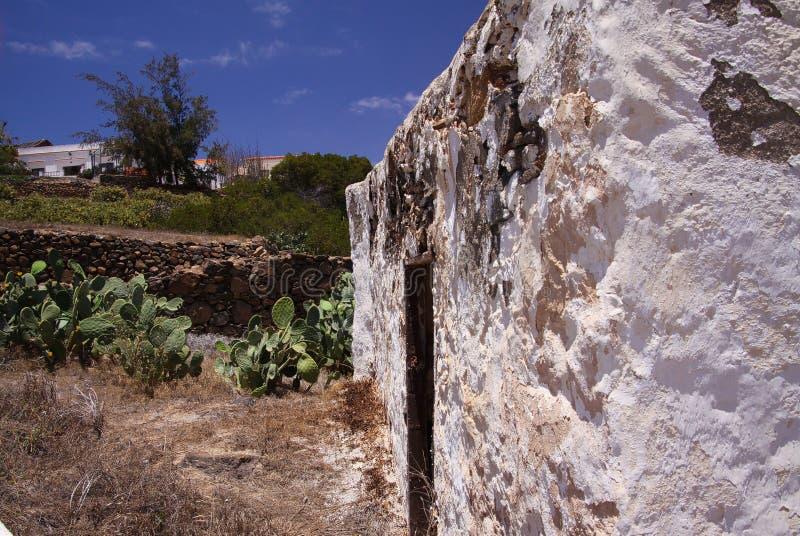 BETANCURIA FUERTEVENTURA - JUIN 14 2019: Sikt längs väggen av det gamla vita lantgårdhuset med kaktusträdgården mot blå himmel arkivbild