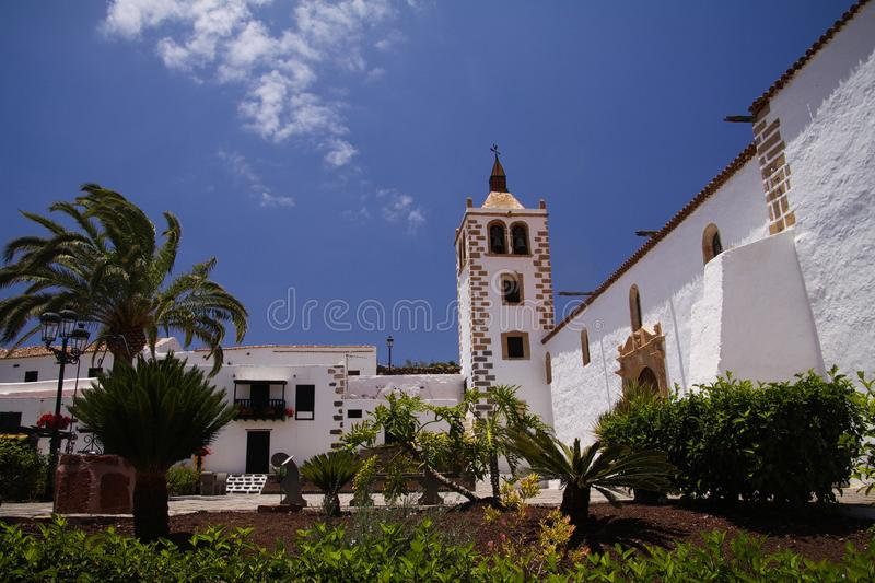 BETANCURIA, FUERTEVENTURA - JUIN 14. 2019: View over garden with palm trees on old white church with clock tower against blue sky stock images