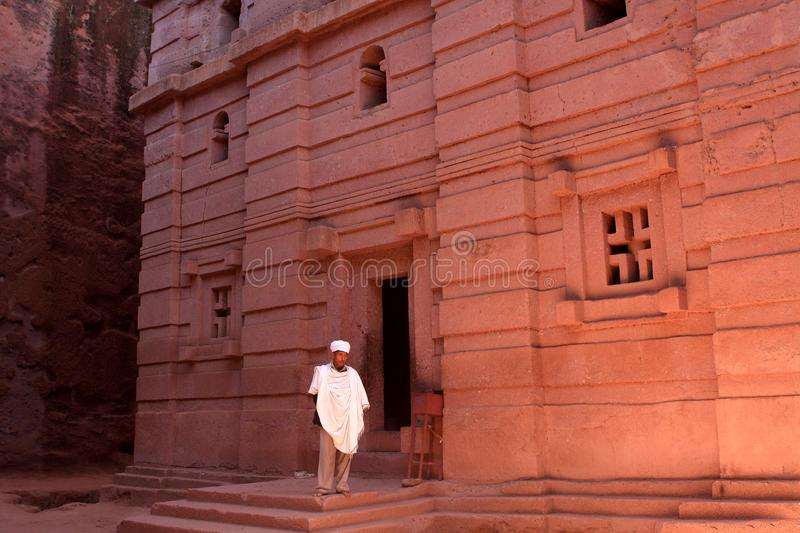 Bete Amanuel, Rock-Hewn Church At Lalibela, Ethiopia, East Africa. A priest dressed in white stands by the door of his church. Rock-hewn church of Bete Amanuel stock photography