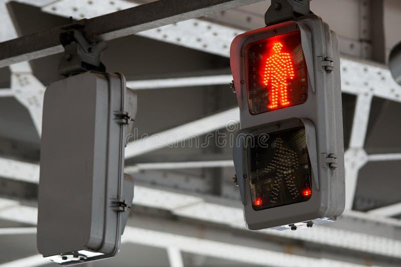 Betecknar korsningen övergångsställekorsning ljus som visar röda ljus, korsningen kors För skullen av folket som använder trottoa arkivfoton