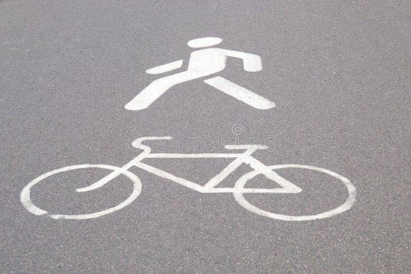 Beteckning av en cykelbana och en fot- gångbana som målas på asfalt fotografering för bildbyråer