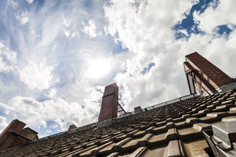 Betegeld dak met donkeroranje bakstenen en gele schoorstenen tegen D stock foto