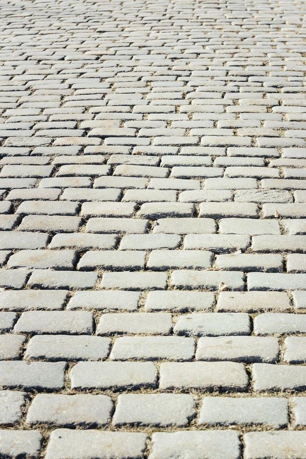Betegeld met het fragment van de weg van straatsteenbakstenen als abstracte achtergrond stock foto's