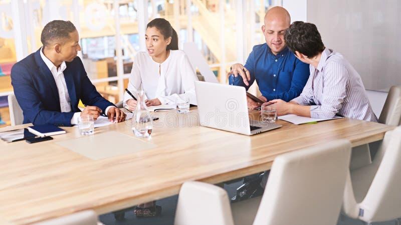 Beteiligte Diskussionen zwischen Unternehmensleitern in der Sitzung am Konferenztische stockbild