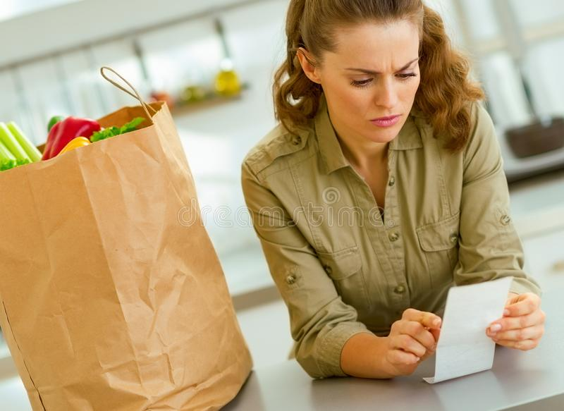 Beteiligte Hausfrau, die Rechnung nach dem Einkauf in der Küche überprüft stockfoto