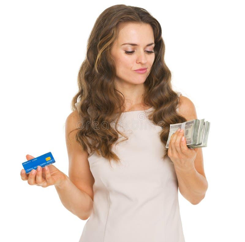 Beteiligte junge Frau mit Kreditkarte und Dollar stockbilder