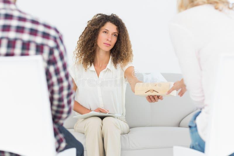 Beteiligter Therapeut, der der Frau ein Gewebe an der Paartherapie übergibt lizenzfreies stockfoto