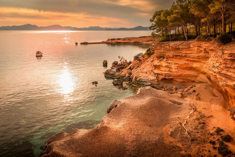 Betel, blisko Colonia De Sant Pere, zatoczka, wpust, łódź, jacht, drzewa, plaża, natura, półmrok, zmierzch, odbicie na morzu śród fotografia royalty free