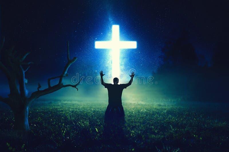 Beten vor dem Kreuz stockbilder