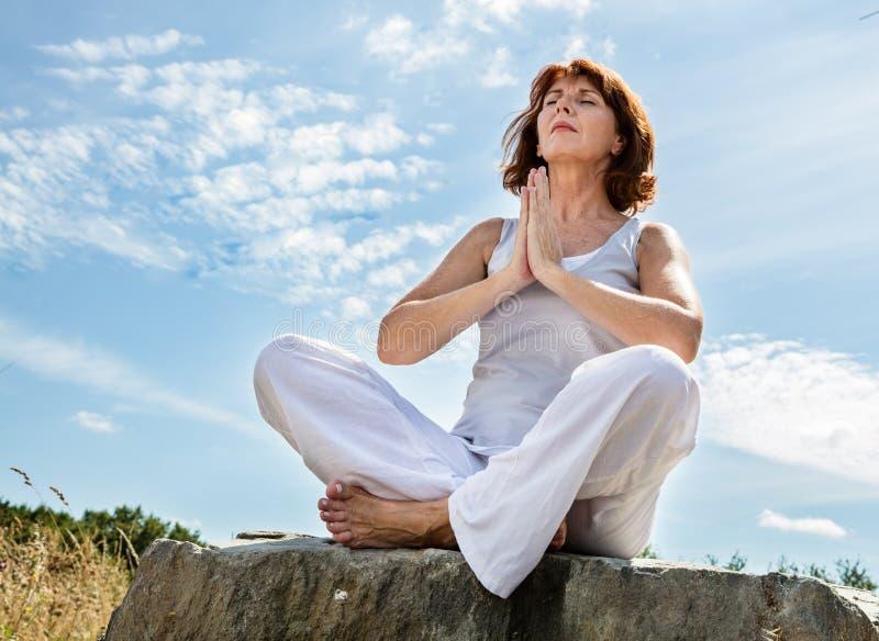 Betende schöne mittlere Greisin in Yogaposition über blauem Himmel stockbilder