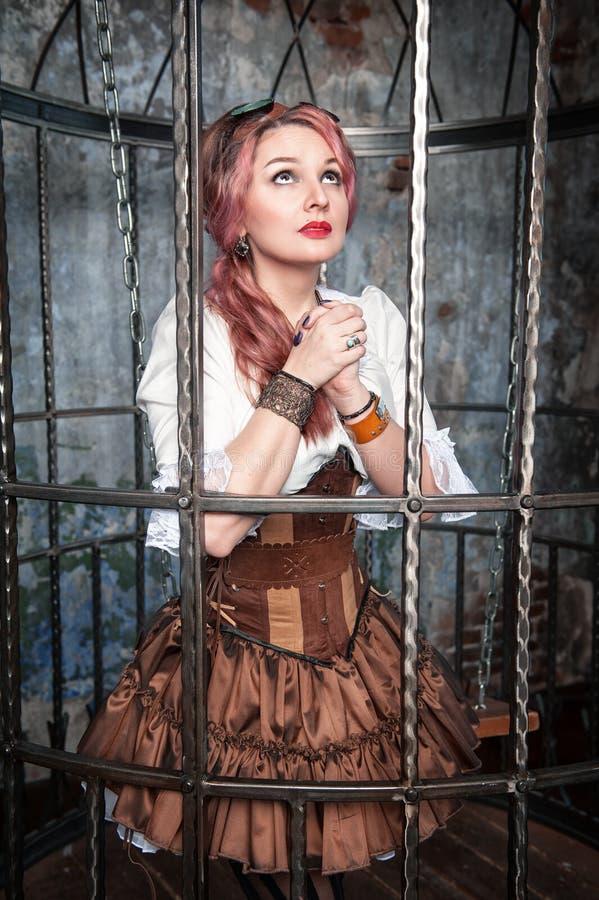 Betende schöne steampunk Frau im Käfig stockbilder