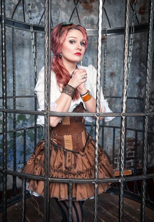 Betende schöne steampunk Frau im Käfig lizenzfreie stockbilder
