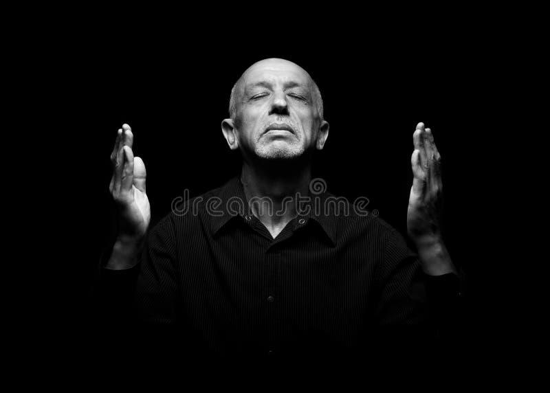 Betender älterer Mann mit geschlossenen Augen und den angehobenen Händen oben stockfoto