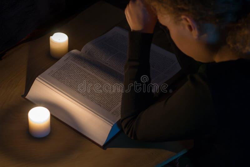 Betendes Mädchen über der Bibel mit einem Kreuz durch Kerzenlicht lizenzfreies stockfoto