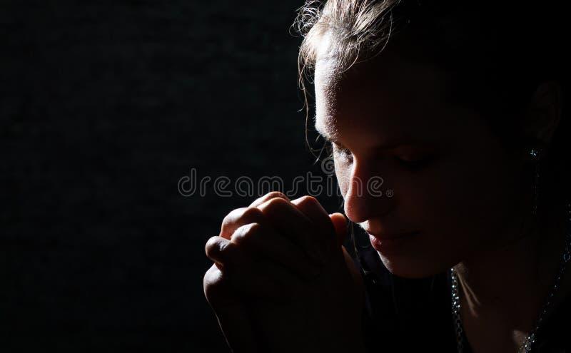 Betendes Porträt der jungen Frau auf Dunkelheit lizenzfreie stockfotografie