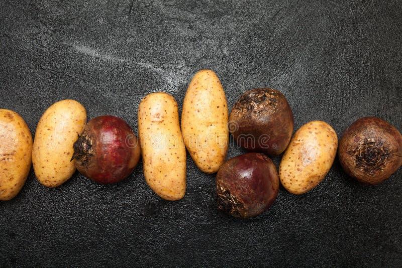 Beterraba vermelha e batatas em um fundo preto imagem de stock royalty free