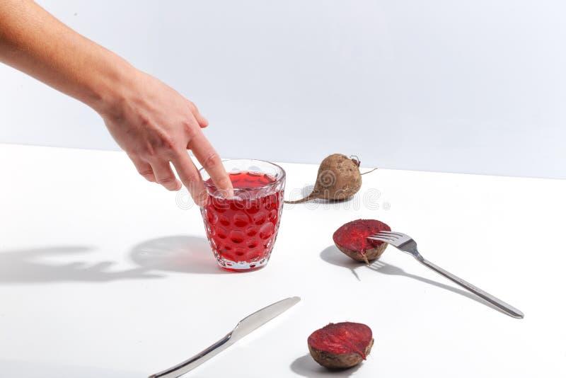 Beterrabas cruas e um vidro do suco em uma tabela branca Conceito minimalistic criativo foto de stock