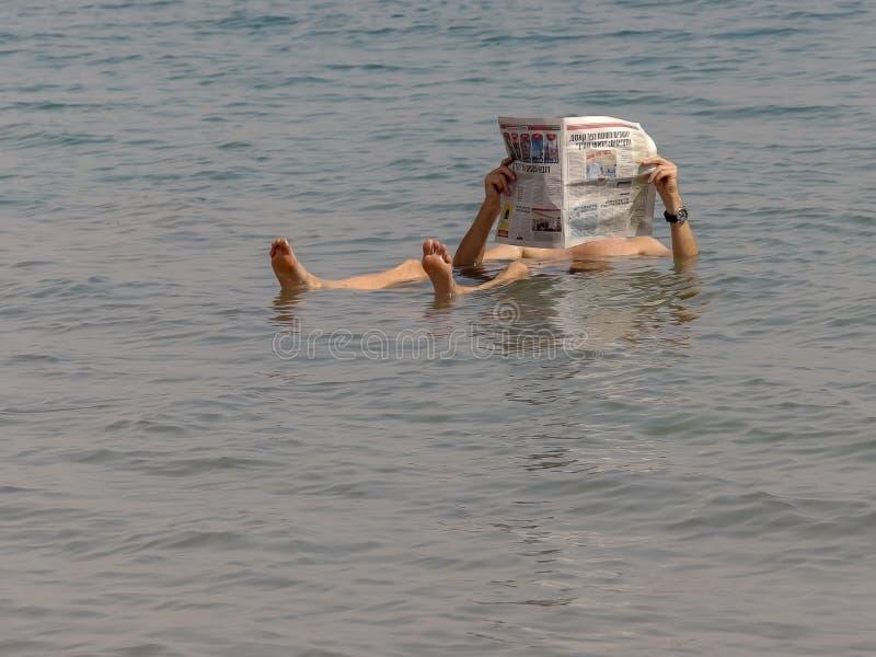 BETHLEHEM, PALESTINA 22 SEPTEMBER, 2016: een mens drijft in het dode overzees van Israël en leest een krant stock fotografie