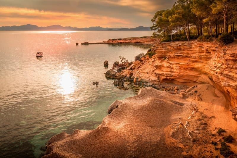 Betlem nära Colonia De Sant Pere, liten vik, öppning, fartyg, yacht, träd, strand, natur, skymning, solnedgång, reflexion på mede royaltyfri fotografi