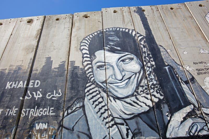 Betlemme - il dettaglio del graffitti sulla barriera di separazione Donna palestinese con l'arma immagini stock