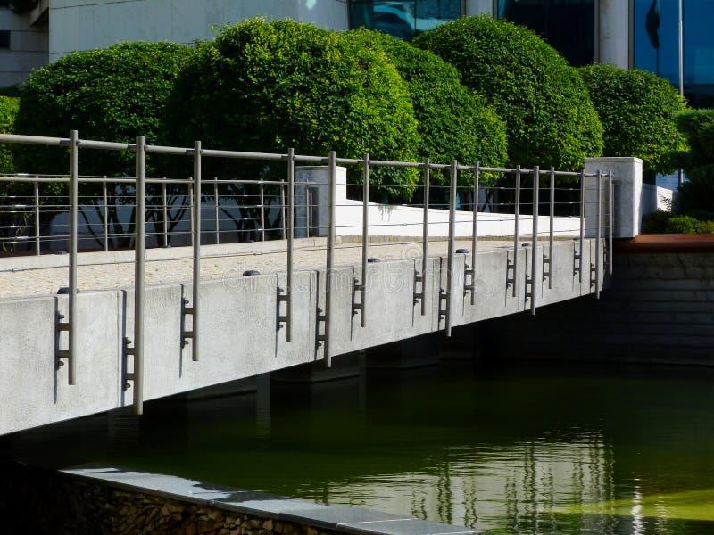 Beton en staal de voetbrug met weelderig groen gebied vormde kleine bomen in openbaar park royalty-vrije stock afbeeldingen