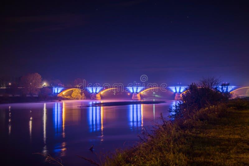 Betonbrücke mit schönen blauen Lichtern, die nachts in Pavia, Italien, im See reflektiert werden stockfotografie