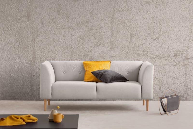 Betongvägg i moderiktig vardagsrum som är inre med den gråa scandinavian soffan, tidningskuggen och kaffetabellen med den gula to arkivbilder