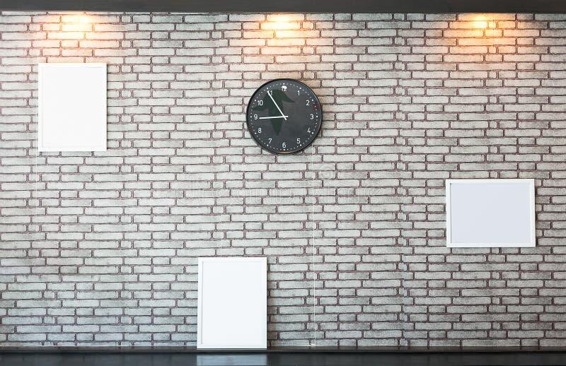 Betongvägggarnering med en bildram och klocka arkivfoto