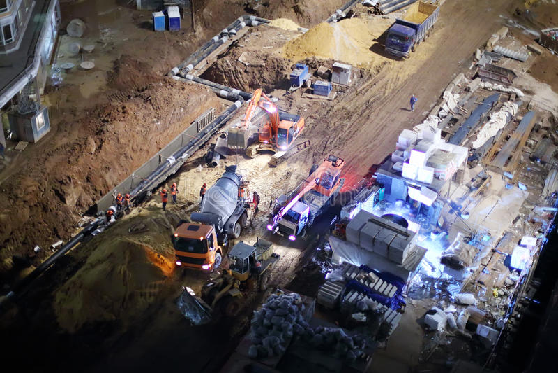 Betonmischer, Kran und Planierraupe an der Baustelle stockbilder