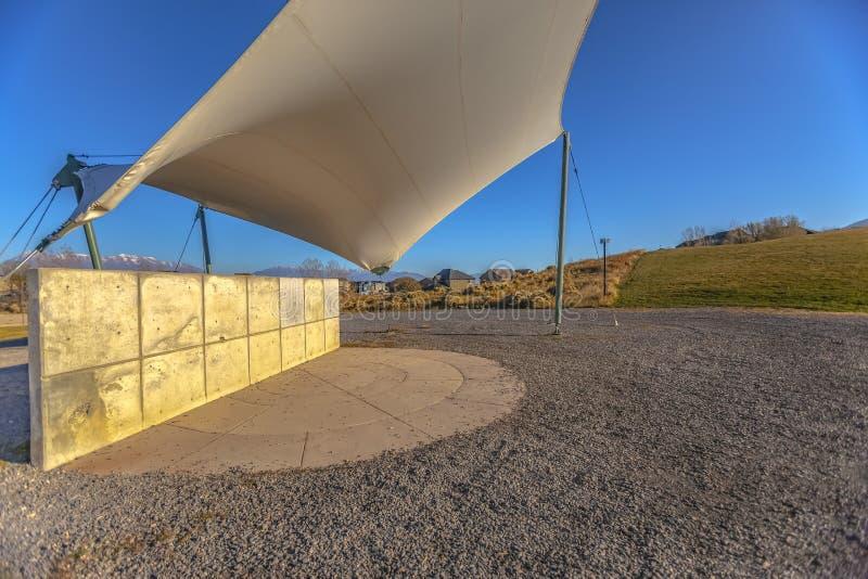 Betonowa prostokątna struktura na skalistej ziemi pod białym baldachimem zdjęcie stock