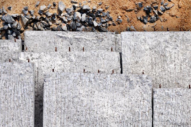 Betonowe płyty wypiętrzają, tekstury betonowy tło, beton dla robot budowlany na piasku i kamienie, fotografia royalty free